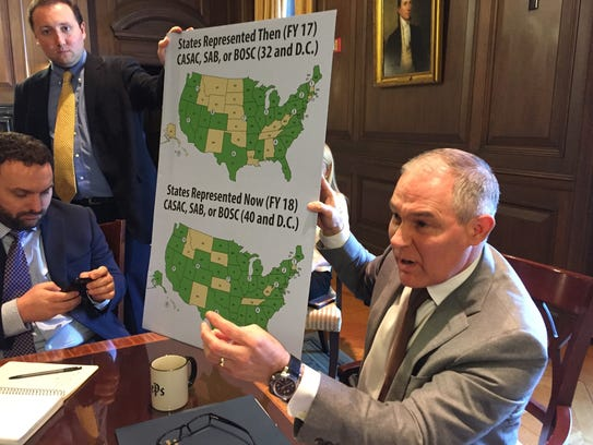 EPA Administrator Scott Pruitt holds up a poster showing