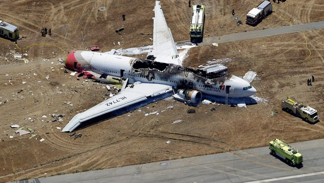 In this Saturday, July 6, 2013 aerial photo, the wreckage of Asiana Flight 214 lies on the ground after it crashed at the San Francisco International Airport.
