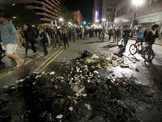 Protesters march past burned garbage in downtown Oakland, Calif., on Wednesday, Nov. 9, 2016. President-elect Donald Trump's victory set off multiple protests. (Jane Tyska/Bay Area News Group via AP)