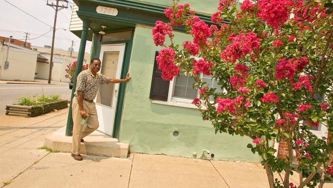 Wilmington activist Eric Robinson is shown here in 2006 with the Crepe Myrtle on Heald Street he had a hand in planting.