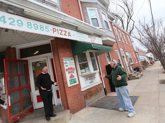 Paul Calistro, executive director of West End Neighborhood House, stops by to talk with longtime owner Bernie Malloy of Bernie's Double Slice on the corner of West Eighth and Dupont streets.