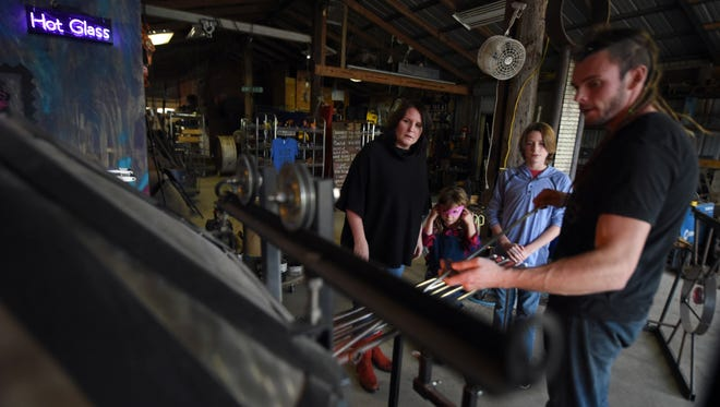Jeremy Thomley, 34, shows the Butler family the process of making glass in the Mohawk Steel & Glass Co. working shop located at the Thomley's Christmas Tree Farm in Hattiesburg.