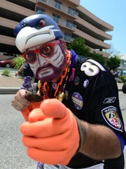 A decked out Ravens fan walks in the Ravens Roost parade
