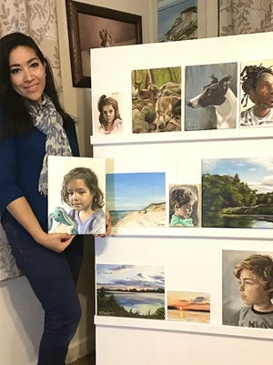 Artist Nastassia Hunter of Grafton holds her winning oil portrait of her daughter in the 2020 Small Stones Festival of the Arts.