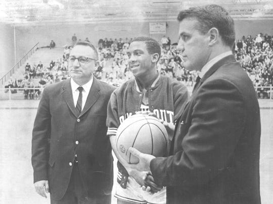 Ron Kornegay receives a basketball commemorating his 1,000th point during his sophomore season in 1967 from assistant coach Godfrey (Buzz) Buzzelli with team trainer. Ermio J. (Mim) Truppa, standing by (left).