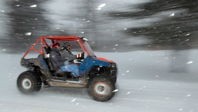 The snow was a headache for many, but Dominic and Abby Russo, of Green Township, took advantage of the opportunity for a snowy ride in their all-terrain vehicle.