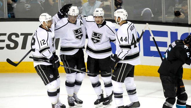 Los Angeles Kings center Anze Kopitar (11) is congratulated by right wing Marian Gaborik (12), defenseman Slava Voynov (26), and defenseman Robyn Regehr (44) after scoring a goal against the San Jose Sharks during the first period in game five of the first round of the 2014 Stanley Cup Playoffs at SAP Center at San Jose.