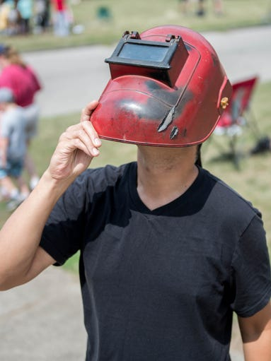 Elias Soriano uses a welding mask to look at the solor