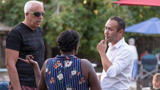 Democratic congressional candidate Andrew Janz, right, talks with Patrick Mendes, left, Sandra Mathis of Tulare and other supporters during a barbecue at a Visalia home on Friday, July 13, 2018.