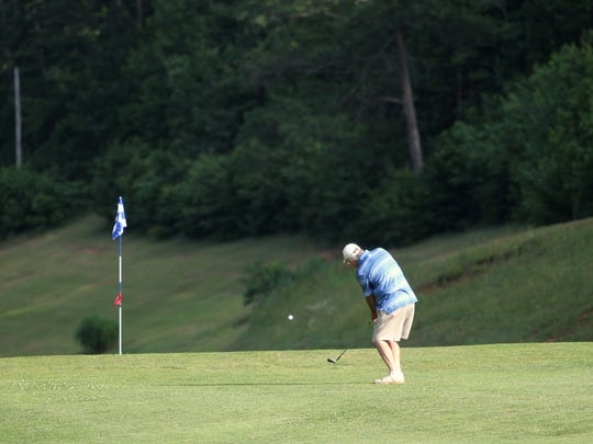 Jerry Dotson chips onto the green during a morning