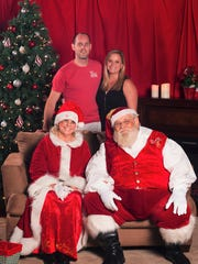 1228YNHoldy.jpg - Tim and Brittany Holdy, standing, hosted a Toys For Tots/White Doves Holiday Project benefit at their home in The Pines subdivision in Jensen Beach. Even Mrs. and Santa Clause came to the event.