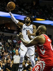 October 11, 2107 - Memphis Grizzlies guard Mike Conley goes for a layup against Houston Rockets forward PJ Tucker during the second quarter at FedExForum on Wednesday night.