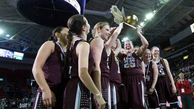 Loyal hoists their championship trophy after their WIAA girls basketball Division 5 state championship.