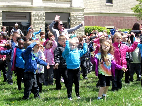 Students and staff dance outside Finn Academy during a celebration Monday.