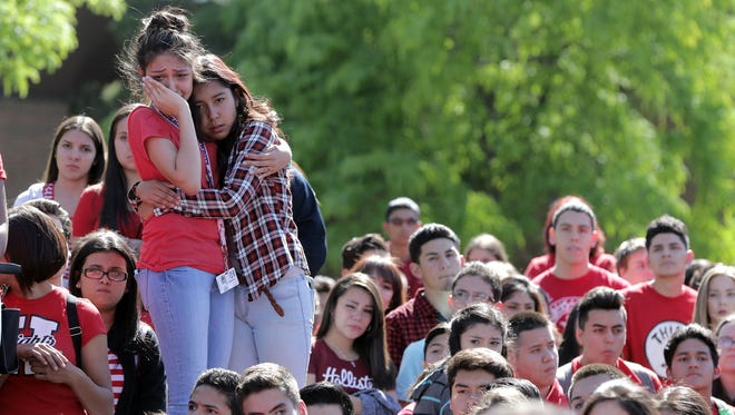 Hanks High School students Olivia Martinez, left, and Adelyn Galvan hold each other recently as they gather with classmates to remember Samantha Aguilar, 16, who died after an accident April 29 on the Sizzler carnival ride at a Día de los Niños celebration at St. Thomas Aquinas Catholic Church. Students released hundreds of red balloons with messages tied to the strings.