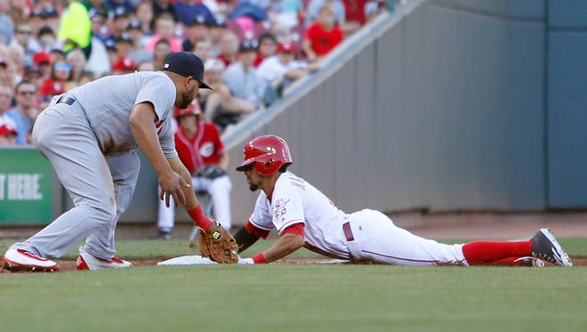 Cincinnati Reds center fielder Billy Hamilton steals third against St. Louis Cardinals third baseman Jhonny Peralta during the second inning at Great American Ball Park.
