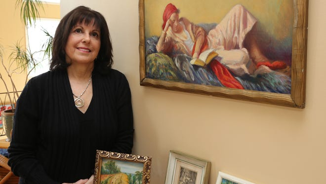 Miriam Morris, daughter of painter David Friedmann, with some of his work at her home.