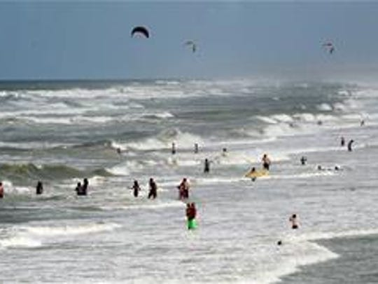People enjoy the beach and heavy surf Wednesday July 2, 2014, at Jacksonville Beach, Fla.