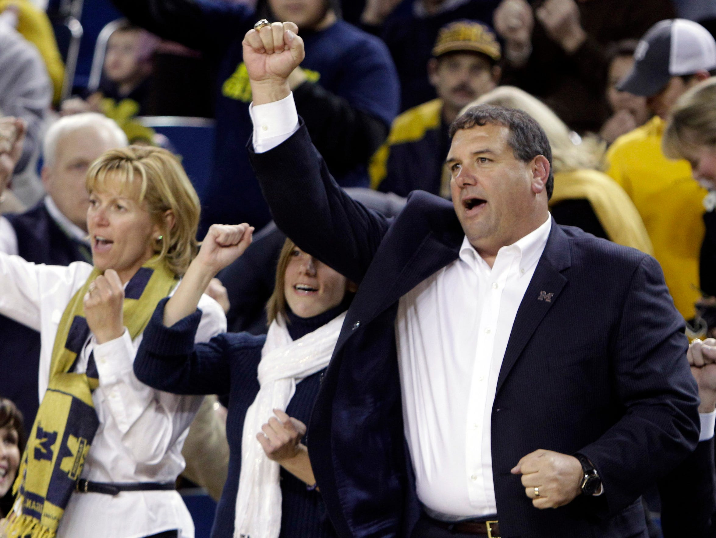 Michigan football coach Brady Hoke, right, after being