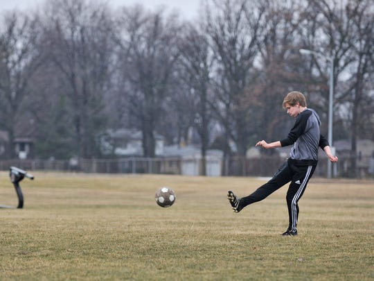 Despite the dampness, Jac Stelly, 15, of Royal Oak, a member of the U. of D. Jesuit High School soccer team, practices his soccer skills near Royal Oak High School Sunday.