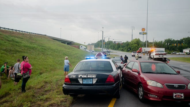 Montgomery Police officers and firefighters respond to a car accident scene on the I-65 south ramp at West Blvd on Friday, June 26, 2015 in Montgomery, Ala.