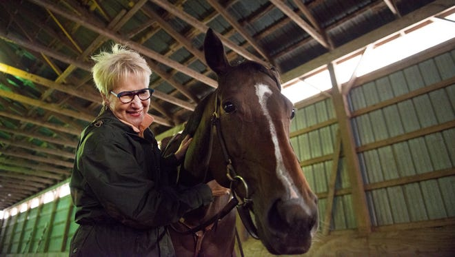 Candy Shira of Pittsford enjoys spending time with Kiki, one of her two rescue horses that she keeps at Fox Hollow Farm in Macedon.