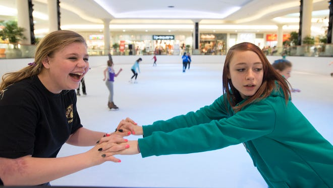 Ashley Smith, left, skates with her friend, Hannah Jones, on Saturday, Feb. 20, 2016, in the Eastdale Mall in Montgomery, Ala. When Smith was an infant her mother put her in a hot oven, causing third degree burns on her body. She has made a recovery, going through 28 surgeries.