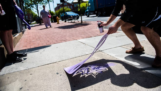Adam Rudel, marketing and football outreach coordinator with the Baltimore Ravens, lifts a Ravens logo stencil after spraying the chalk logo on the sidewalk on Chambersburg Street in Gettysburg on Friday.