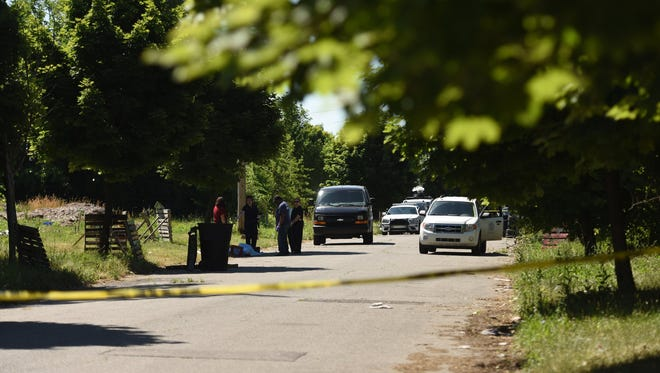 Police investigate a crime scene Tuesday, June 21, 2016, near Chandler Park on Detroit's east side where a women's body was found naked in the street.