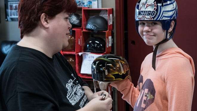 Abbie Kopf with her mother Vicki show a custom painted Batman helmet painted by Hot Rods and Handlebars for Abbie.