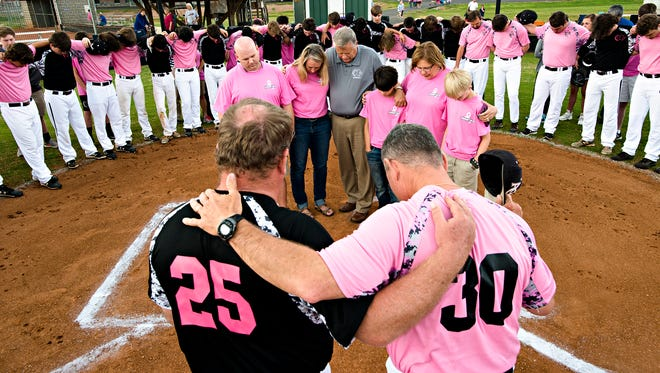 """Prattville Christian head coach Brad Sansom, bottom left, and Alabama Christian Academy head coach Don Gilliam, bottom right, pray together with their teams and fans for, from left, Patrick Osborne, his wife, Tara Osborne, embraced by Prattville Christian headmaster Ron Mitchell, the Osborne's son, Carson Osborne, 13, embraced by Jennifer Mitchell and the Osborne's son, Cooper Osborne, 11, on Monday, March 27, 2017 before the baseball game between Prattville Christian and Alabama Christian in Prattville, Ala. Tara Osborne is diagnose with Breast Cancer and the game was played in her honor. """"Its very humbling, it's very special, they'll never know how much it means to me,"""" Tara Osborne said."""