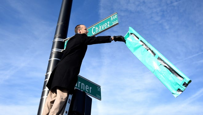 Lansing Mayor Andy Schor unveils the Cesar E. Chavez Avenue sign that replaces the Grand River Avenue during a ceremony on Tuesday, Jan. 3, 2018, at the intersection of Cesar E. Chavez Avenue and Turner Street in Old Town Lansing.