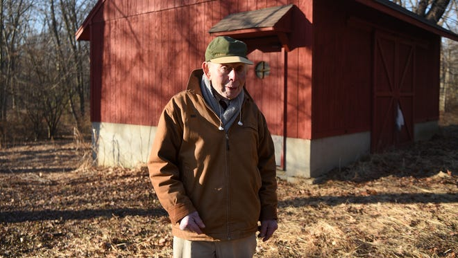 Bud Schwartz walks through a portion of the 12.2 acres of undeveloped land that he and his wife Alice sold to Franklin Lakes. Behind Bud is a barn containing hay. Until a few years ago, the couple kept horses on the property.