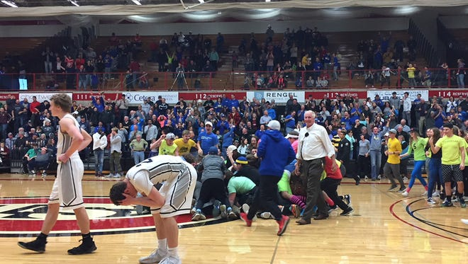 Fans mob St. Cloud Cathedral's Nick Schaefer after he hit the winning shot as time expired Friday night at Halenbeck Hall. Distraught Eden Valley-Watkins players walk off the court after the 55-54 loss.