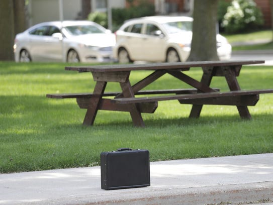 A briefcase sits on the sidewalk in front of the Outagamie