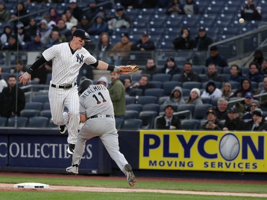 New York Yankees first baseman Tyler Austin can't come up with the wide throw from shortstop Didi Gregorius, allowing Miami Marlins' J.T. Realmuto (11) to reach first base safely and Starlin Castro to score during the first inning of a baseball game Tuesday, April 17, 2018, in New York. (AP Photo/Julie Jacobson)