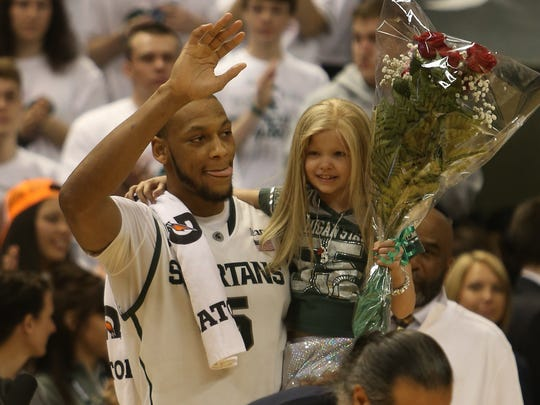 Michigan State senior center Adreian Payne carries his special guest Lacey Holsworth onto the court where he was honored with fellow seniors on March 6, 2014, at the Breslin Center in East Lansing.