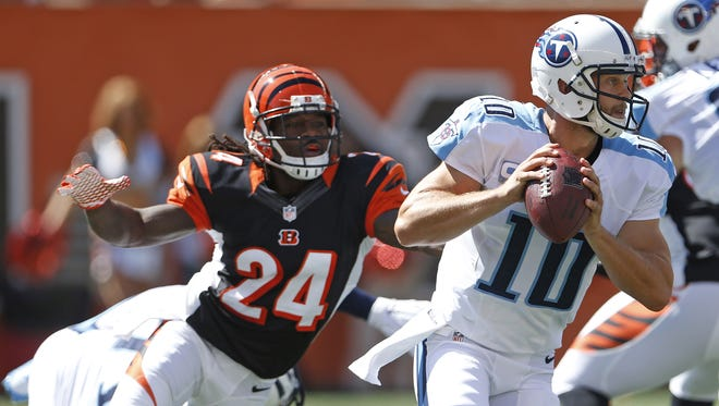 Tennessee Titans quarterback Jake Locker (10) is chased out of the pocket by Cincinnati Bengals cornerback Adam Jones (24) during the first quarter at Paul Brown Stadium in downtown Cincinnati Sunday.