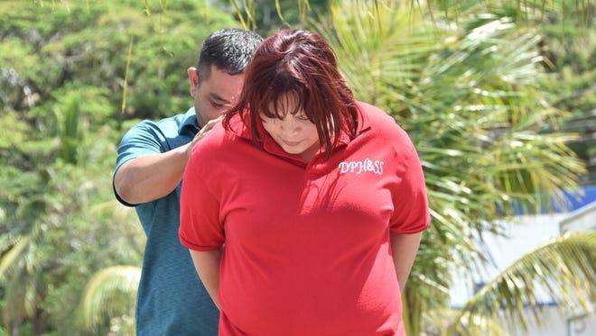 Vera Marie Ulloa Del Rosario is escorted to the Guam Police Department Hagatna precinct upon her arrest Wednesday, April 20. Masako Watanabe/Pacific Daily News/mwatanabe@guampdn.com