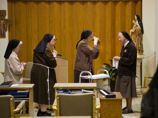 Sister Jane Marie DeLand, from left, Sister Catherine Kiske Janeway, Sister Marie Carmel Fisk, Sister Jeanne Maffet, and Sister Mary Veronica Jonkier, receive communion during daily mass at the Monastery of St. Clare in Evansville, Thursday, Jan. 19, 2017.