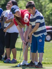 Jordan Britt gives Jonathan Calderon some putting tips as part of a Symetra Tour FireKeepers Championship Kids Clinic earlier this week at the Battle Creek Country Club.