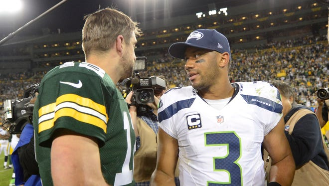Green Bay Packers quarterback Aaron Rodgers (12) meets quarterback Russell Wilson (3) after the game against the Seattle Seahawks at Lambeau Field.