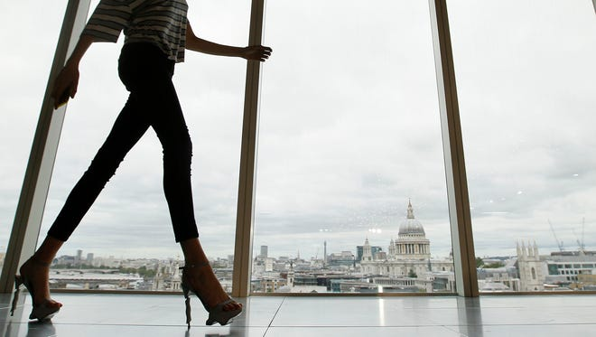 A model walks past a window with a view of St Paul's Cathedral during the presentation of the Matthew Williamson Spring/Summer 2013 collection at London Fashion Week on Sept. 16, 2012.