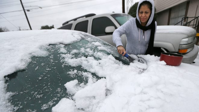 Laura Perez scrapes ice off of her car as she prepares to drive to work in icy conditions Dec. 6, 2013, in Dallas.