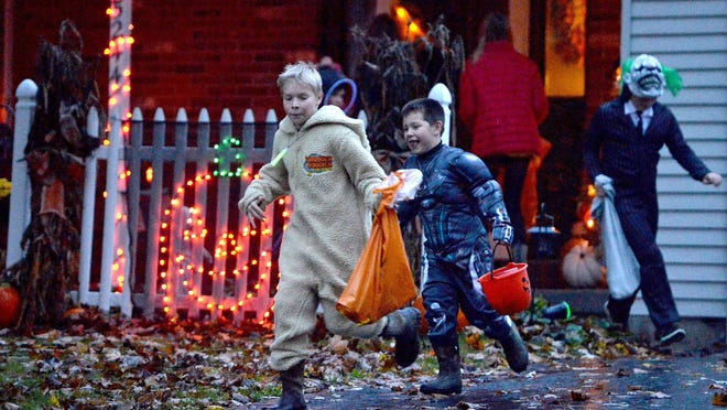 Lewis Hoehn, center left, Owen Turner, center right, Ryan Benoit, far right, and Jacob Block, background, run from house to house in the Georgetown Heights subdivision of McKean Township during Halloween trick-or-treat activities in 2018.