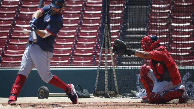 Boston Red Sox's Mitch Moreland bats as Jonathan Lucroy catches during practice on Sunday.