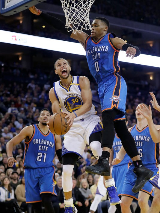 Golden State Warriors' Stephen Curry (30) is fouled while driving to the basket by Oklahoma City Thunder's Russell Westbrook (0) during the second half of an NBA basketball game Wednesday, Jan. 18, 2017, in Oakland, Calif. (AP Photo/Marcio Jose Sanchez)