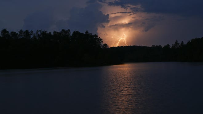 Lightning illuminates the clouds and is reflected in the surface of Lake Nicol in Tuscaloosa on Monday, July 20, 2020. Scattered showers and thunderstorms are possible throughout the rest of the week in the Tuscaloosa area. Wednesday's high temperature will be in the mid-90s, with a heat index of near 105 degrees possible.