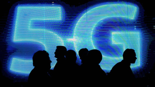 Visitors walk past a 5G logo during Mobile World Congress in Barcelona.