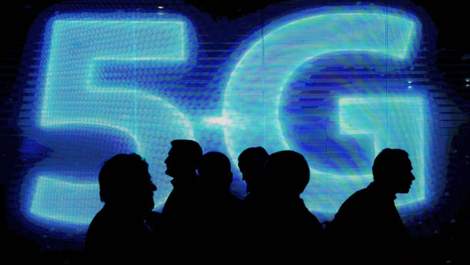 Visitors walk past a 5G logo during the Mobile World Congress in Barcelona, on March 1, 2017.  Phone makers will seek to